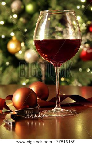 Glass of red wine on table with holiday tree in background