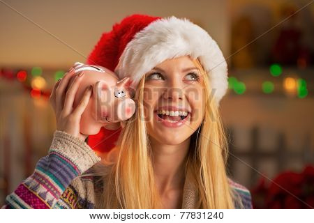 Portrait Of Smiling Teenager Girl In Santa Hat With Piggy Bank