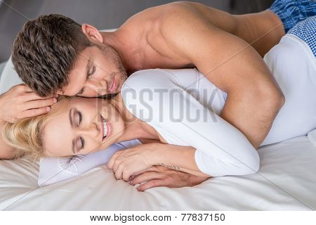 Close up Romantic Young Couple Lying on White Bed with Handsome Topless Guy Embracing her Beautiful Smiling Partner in Long Sleeve Shirt.