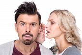 Amazed man is listening gossip in the ear from woman on the white background. poster