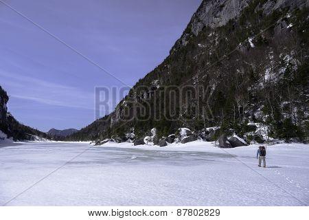 Man Trecking Across A Frozen Lake