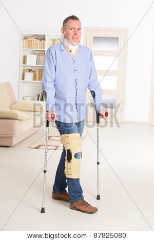 Man with leg in neck brace, knee cages and crutches for stabilization and support