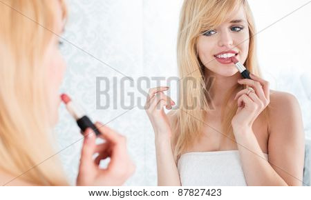 Young Smiling Blond Woman Looking Into Mirror and Applying Lipstick, Getting Ready to Go Out