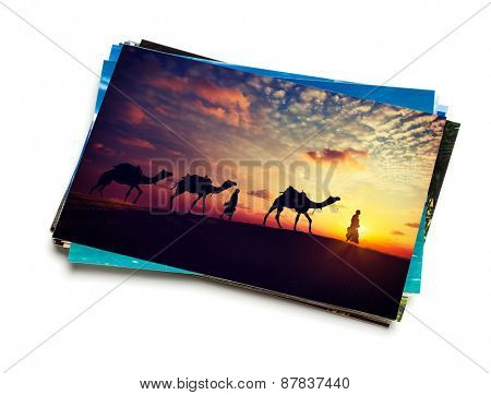 Holidays travel concept creative background - stack of vacation photos with camel caravan sunset image on top isolated on white background