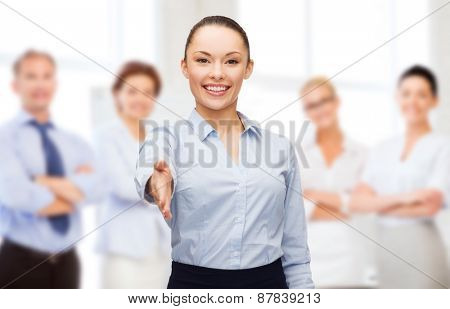 business, gesture and education concept - friendly young smiling businesswoman with opened hand ready for handshake over group of people background