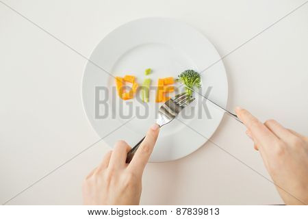 healthy lifestyle, diet, vegetarian food and people concept - close up of woman with fork and knife eating vegetable letters on plate