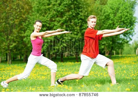fitness man and woman doing physical stretching exercises during outdoors sport training
