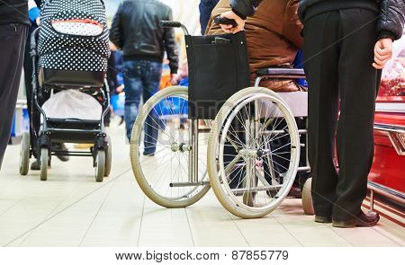 wheelchair bound invalid buyer in shopping center with assistant