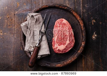 Raw Fresh Marbled Meat Black Angus Steak Ribeye And Meat Fork On Dark Background