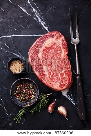 Raw Fresh Marbled Meat Black Angus Steak Ribeye, Seasonings And Meat Fork On Dark Marble Background