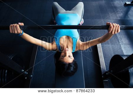 Young fit woman working out with barbell on bench in the gym. Bar Bench Pres