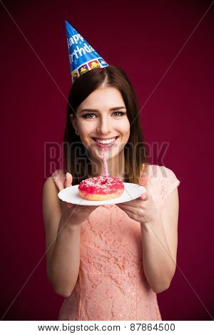 Smling young woman holding donut with candle over pink background and looking at camera