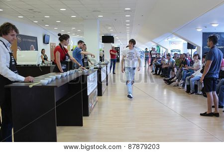DNEPROPETROVSK, UKRAINE - MAY 31, 2013: Russian champion in cup tasting Dmitry Boroday (in center) acts as commentator during 5th Ukrainian Cup Tasters Championship