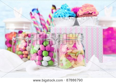 Multicolor candies in glass jars and cupcakes on color wooden background