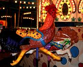 rooster seat on carnival carousel with lights and mirrors. poster