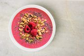 Smoothie bowl with raspberries granola and chia seeds on a white granite background overhead view poster