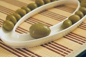 Spanish olive with small at the plate on a table-napkin of Bambu poster