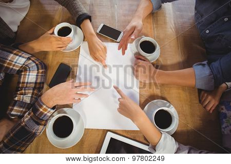Friends discussing and drinking coffee at coffee shop