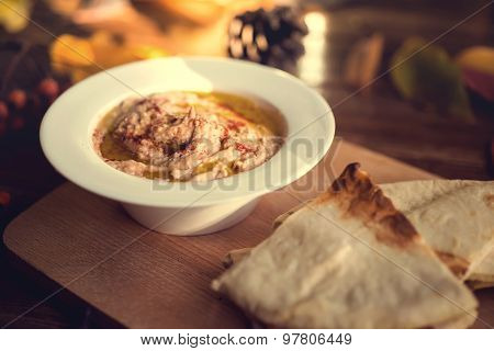 Plate with hummus dip and pita bread, a common tapas or starter dish on wooden background. Autumn co