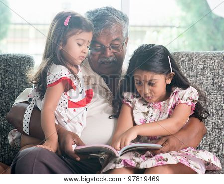 Asian grandfather and granddaughters reading story book. Happy Indian family at home. Grandparent and grandchildren indoor lifestyle. poster
