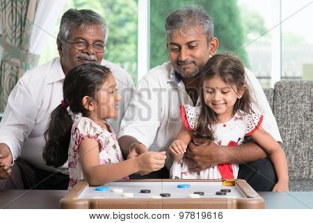 Happy multi generations Asian Indian family playing carom game at home. Grandparent, parent and children indoor lifestyle.