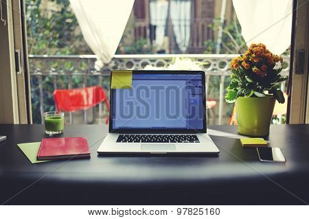 Blogger needs workstation workplace with open laptop smartphone, note book and pot of flowers