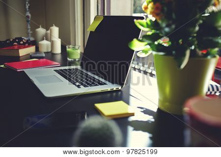 Modern workplace with open laptop computer, smartphone, note book and pot of flowers