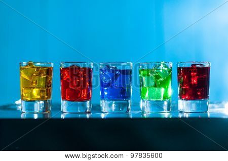 Five glasses with alcohol cocktail on the bar at nightclub, blue background
