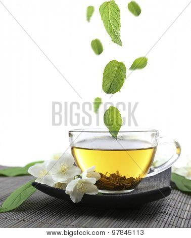 Mint leaves falling in cup of jasmine tea isolated on white
