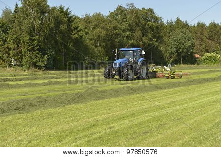 Agriculture, The Kidding Of Shaken Grass With Blue Tractor With Kidder.