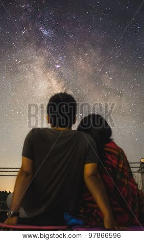 Sweet couple stargazing towards the Milky Way galaxy