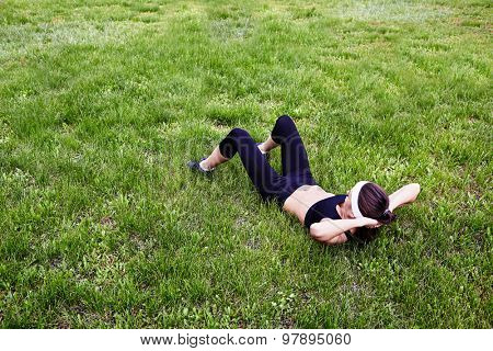 Sporty girl doing situps on green lawn