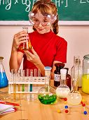 Child in red holding flask in chemistry class. poster