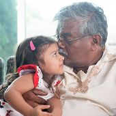Portrait of Indian family at home. Grandparent kissing grandchild. Grandfather and granddaughter. Asian people living lifestyle. poster