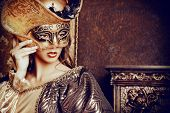 Venetian masquerade carnival. Elegant lady wearing beautiful lush dress and venetian mask stands in a palace room. Renaissance. Barocco. Fashion. poster