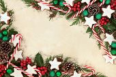 Christmas background border of gingerbread biscuits,  candy canes, bauble decorations, holly and winter greenery over old parchment paper. poster