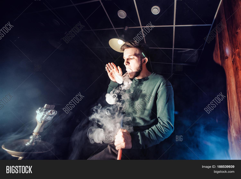 Young handsome guy smoking hookah alone closeup