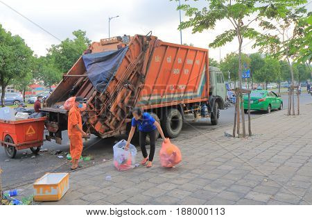 HO CHI MINH CITY VIETNAM - NOVEMBER 28, 2016: Unidentified people collect garbage in downtown Ho Chi Minh city.