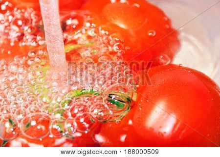Washing ripe red bunch of tomatoes in a glass container using a jet of clean drinking water