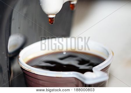 Drops and a jet of strong hot black coffee pouring into a plastic cup from the coffee machine