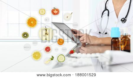 healthy food supplements concept Hand of nutritionist doctor touch digital tablet on symbols fruits background