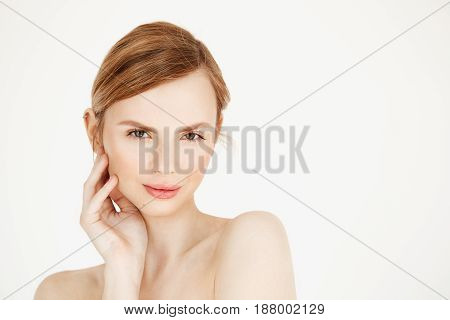 Portrait of young nude beautiful girl looking at camera touching face over white background. Facial treatment. Beauty cosmetology and spa. Copy space.