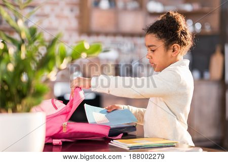 African American Schoolgirl Packing Backpack And Preparing For School, Elementary School Student Con