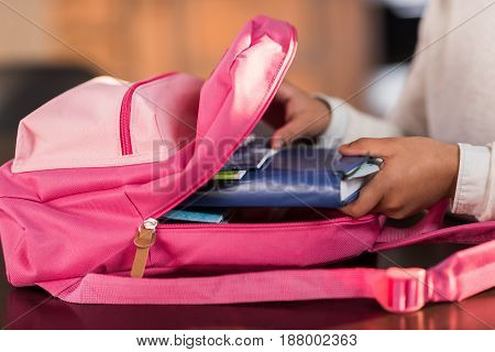 schoolgirl packing backpack and preparing for school elementary school student concept