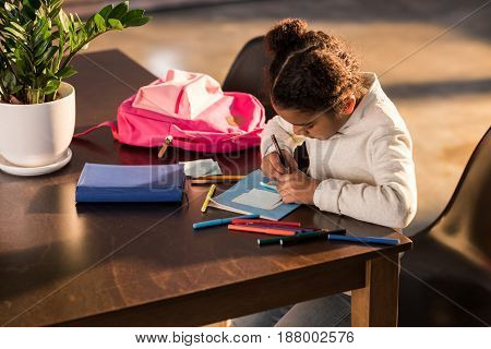 Adorable Little Girl Sitting At Table And Drawing With Colorful Felt Tip Pens, Doing Homework Concep