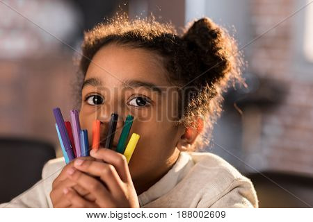 Close-up View Of Adorable Little Girl Holding Colorful Felt Tip Pens And Looking At Camera, Doing Ho