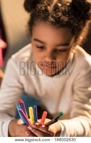 Close-up View Of Adorable Little Girl Holding Colorful Felt Tip Pens, Doing Homework Concept