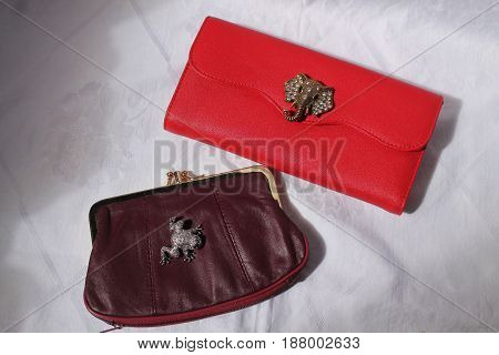 red leather purses decorated with brooches for beautify and luck