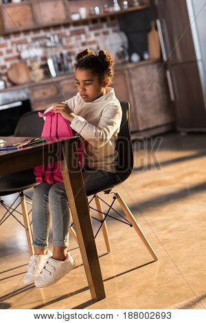 Cute Little Girl Holding Backpack While Sitting At Table With Felt Tip Pens, Doing Homework Concept