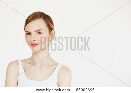 Portrait of young beautiful girl with natural make up smiling looking at camera over white background. Cosmetology and spa. Copy space.